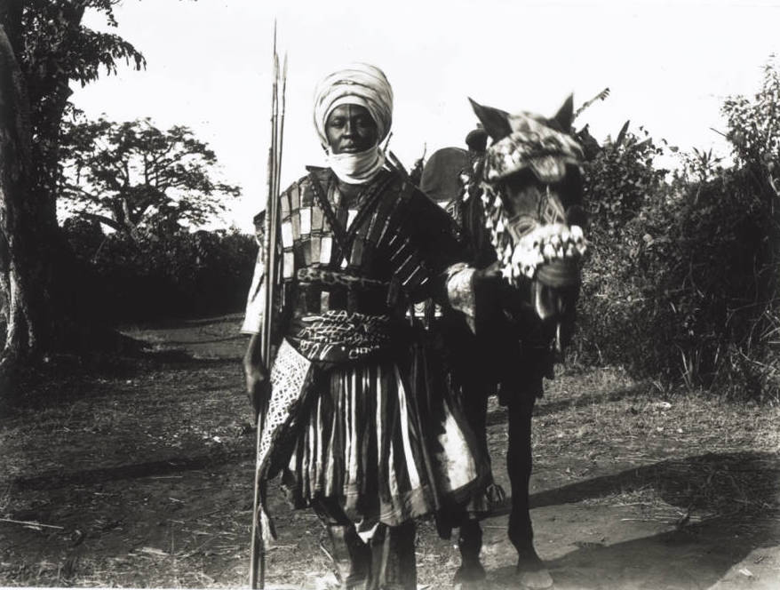 Cameroon_Grassfields_A_brother_of_King_Njoya_His_horse_with_festive_harness_He_himself_is_wearing_.jpg.100f6b270c6fe657818403c3551113b8.jpg